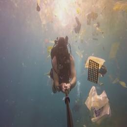 Oceano de plástico, homem nada no mar da Indonésia cercado por lixo
