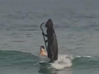 Surfista se fantasia de morte para alertar as pessoas sobre aglomerações